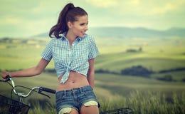 Beautiful vintage girl sitting next to bike, summer time.  royalty free stock photo