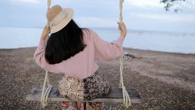 Beautiful vintage woman sitting on a swing. At beach side Stock Images