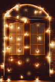 Beautiful vintage wooden door decorated with glowing lamps Stock Photography