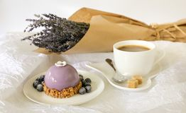 Sweet morning breakfast time concept, beautiful violet cake, blueberries, cup of coffee near bouquet of lavender on. A beautiful violet cake, blueberries, a cup Royalty Free Stock Image