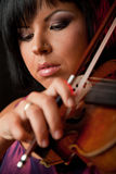 Beautiful violinist. Close-up of a young beautiful woman playing on a violin Royalty Free Stock Photos