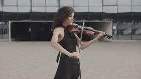 Beautiful violinist in black dress near glass building. Urban art concept stock video