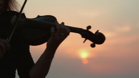 Beautiful violinist playing while the sun is. Beautiful violinist playing while sun is almost gone over the horizon at sea stock video