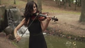 Beautiful violinist plays with inspiration. Girl playing violin in forest. Beautiful violinist plays with inspiration. Young girl in black dress playing violin stock video footage