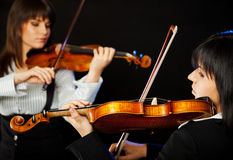 Beautiful violinists. Two beautiful female violinists playing violin isolated on black Stock Image