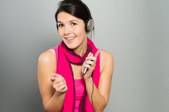 Beautiful vivacious woman listening to music Stock Image