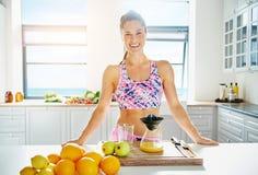 Beautiful vivacious woman preparing fruit juice Royalty Free Stock Images