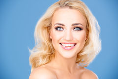 Beautiful vivacious young blond girl. Full of vitality with a fresh healthy skin smiling at the camera on a blue background Stock Photos
