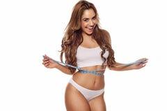 Vivacious woman measuring her waist Stock Photo