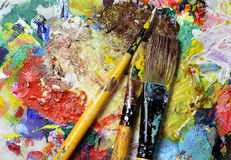 Beautiful vivid art palette and mix of paintbrushes Royalty Free Stock Photos