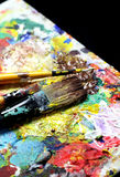 Beautiful vivid art palette and mix of paintbrushes Stock Photos
