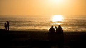 Beautiful vivid beach sunset with silhouetted people over Atlantic Ocean in Vila do Conde, Porto, Portugal royalty free stock photography