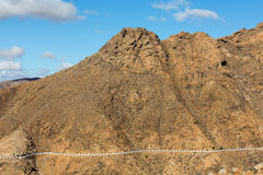 Beautiful volcanic mountains and the road on a mountain slope.  Road from la Pared to Betancuria . Fuerteventura. Royalty Free Stock Photography
