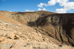 Beautiful volcanic mountains and the road on a mountain slope.  Road from la Pared to Betancuria . Fuerteventura Royalty Free Stock Photos