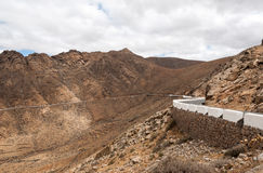 Beautiful volcanic mountains and the road on a mountain slope.  Road from la Pared to Betancuria . Fuerteventura Royalty Free Stock Photography