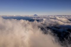 Aerial drone photo - Mt. Fuji rising above the clouds. Beautiful volcano Mt. Fuji rising above an ocean of clouds, as seen from a drone stock image