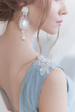 Beautiful volume hairstyle for a bride in a gentle blue light dress with large earrings and adornment in hair. Beautiful volume hairstyle for a bride in a gentle Stock Photo