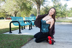 Beautiful, Voluptuous Brunette Outdoors (1). A lovely, voluptuous, young brunette kneels beside park benches outdoors Stock Photography