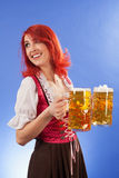 Beautiful wait staff at Oktoberfest. Photo of a beautiful female waitress wearing traditional dirndl and holding two mass beer steins Royalty Free Stock Photography