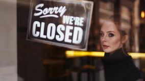 Beautiful waitress comes to the café entrance and flips the open sign to close, then looks around and goes away into stock video footage