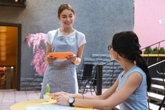 Beautiful waitress feeling worried while having her first day at work. First day. Young beautiful waitress feeling a little bit worried while having her first stock photos