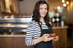 Beautiful Waitress Holding Coffee Cup In Cafeteria Stock Photo