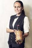 Beautiful waitress offering a bottle of wine Stock Images
