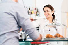 Beautiful waitress serving male customer with a cup of coffee fo Royalty Free Stock Photos