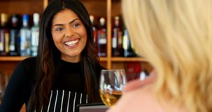 Beautiful waitress serving wine to customer at counter 4k
