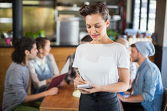 Beautiful waitress standing by customers in restaurant. Beautiful waitress writing while standing by customers in restaurant Royalty Free Stock Photography