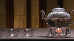 Beautiful warm picture of transparent teapot kettle with tasty green black tea on a table with candles. Glass kettle. With blooming flower tea on wooden table stock footage