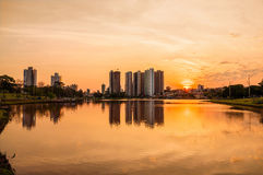 A beautiful warm sunset at the lake with buildings and the city background. Scene reflected on water. Stock Photos