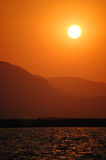 Beautiful warm sunset over mountains and ocean. Fiery red and orange sky during as sun sets in a cloudless sky on the coast in Turkey Royalty Free Stock Image