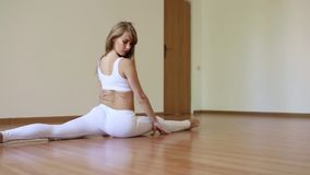 Beautiful girl doing stretching, sitting on the twine stock video footage