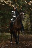 A beautiful warrior girl with a sword wearing chainmail and armor riding a horse in a mysterious forest. A beautiful warrior girl with a sword wearing chainmail royalty free stock images