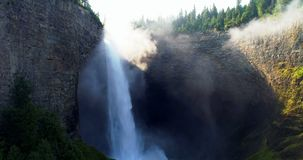 Beautiful water fall through cliff 4k. Beautiful water fall through cliff on a sunny day 4k stock footage
