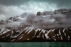 Beautiful water and snow covered mountains in the early morning, Waterfowl Lake Alberta royalty free stock image