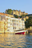 Beautiful water view of City Palace with touristic boat in Udaipur. Beautiful water view of City Palace with touristic boat against blue sky in Udaipur in India Stock Photos