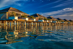 Beautiful water villas on the vibrant blue sea during sunset stock photos