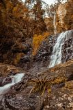 Beautiful waterfall in autumnal forest stock photography
