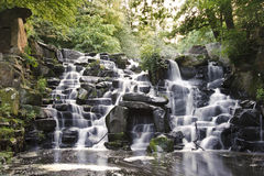Beautiful waterfall cascades over rocks in forest. Waterfall cascades flowing over flat rocks in forest landscape Stock Photo