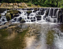 Beautiful waterfall cascades over rocks in forest Stock Photography