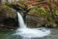 Beautiful waterfall comes out of a huge rock in the forest Royalty Free Stock Images