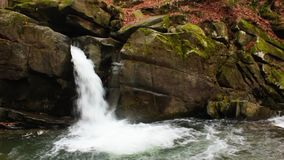 Beautiful waterfall comes out of a huge rock in the forest stock video