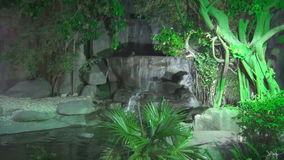 Beautiful waterfall flowing over rocks surrounded by jungle at dusk to light green lantern stock video