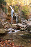 Beautiful waterfall in forest, autumn landscape. Autumn creek woods with yellow trees foliage and rocks in forest mountain stock photos