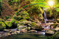 Beautiful waterfall  in the forest. Incredibly beautiful and clean little waterfall with several cascades over large stones in the forest under rainbow comes out Royalty Free Stock Photography