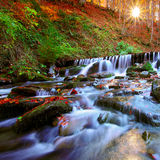 Beautiful waterfall in forest at sunset Stock Photos