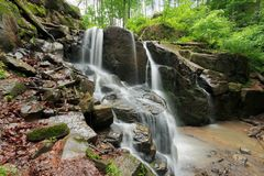 Beautiful waterfall among the huge rocks in forest stock photo