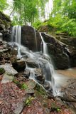 Beautiful waterfall among the huge rocks in forest royalty free stock photography